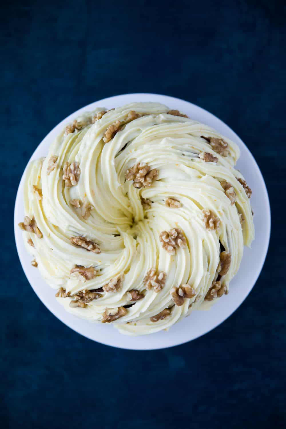 A round carrot cake bundt on a white cake stand.