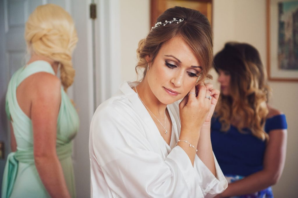 Bride attaching her earrings