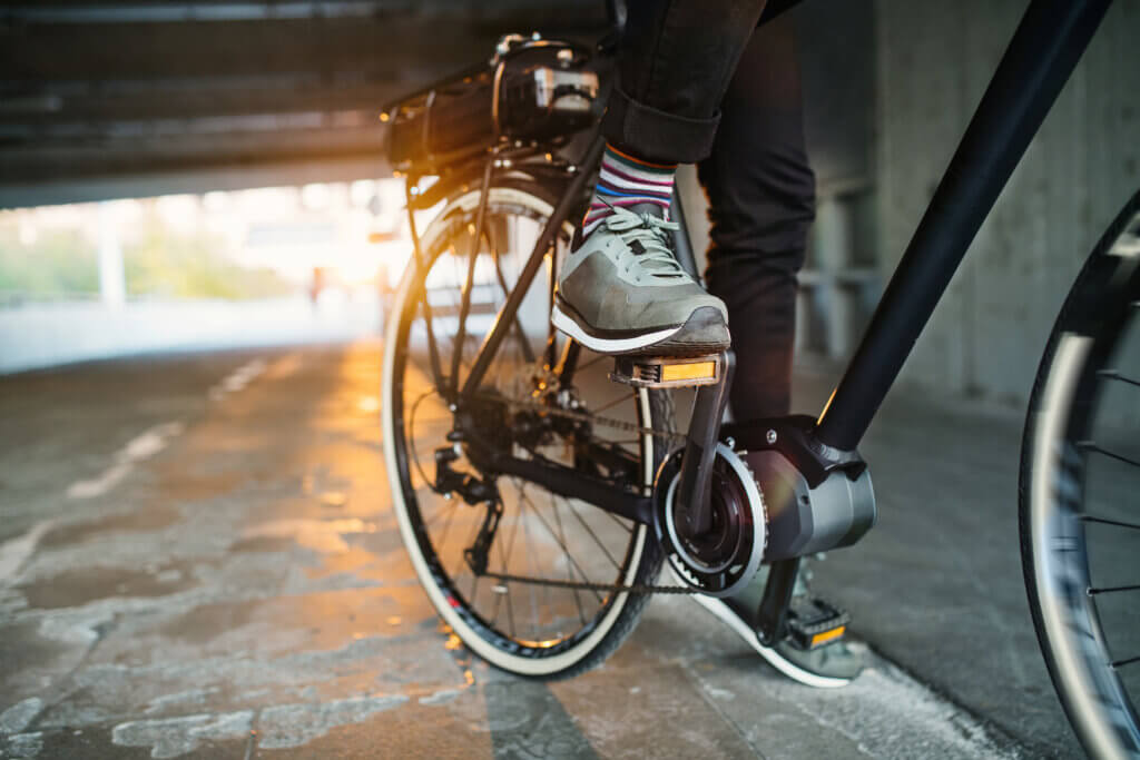 Midsection of businessman commuter with electric bicycle traveling from work in city