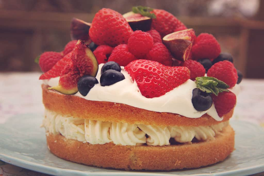 A victoria sponge topped with fresh cream and a variety of fruit