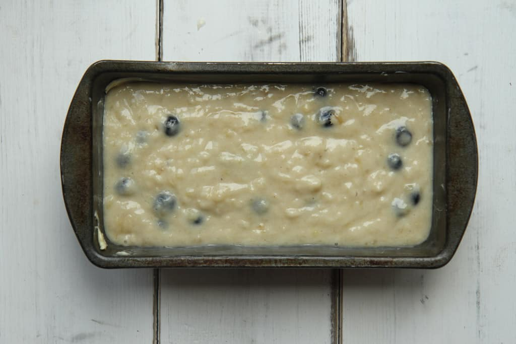 blueberry and banana bread mixture that has been poured into a loaf tin