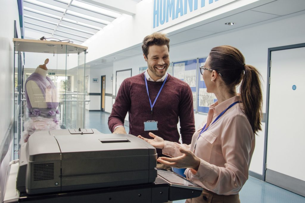Two teachers talking at a copier machine.