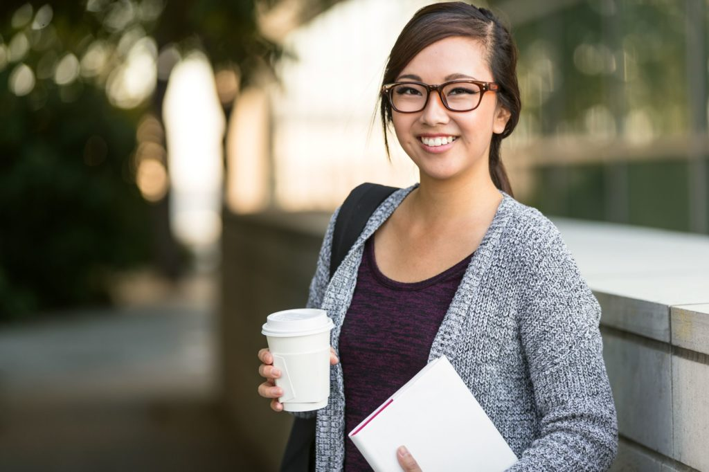 Student with backpack smiling and holding book and coffee.