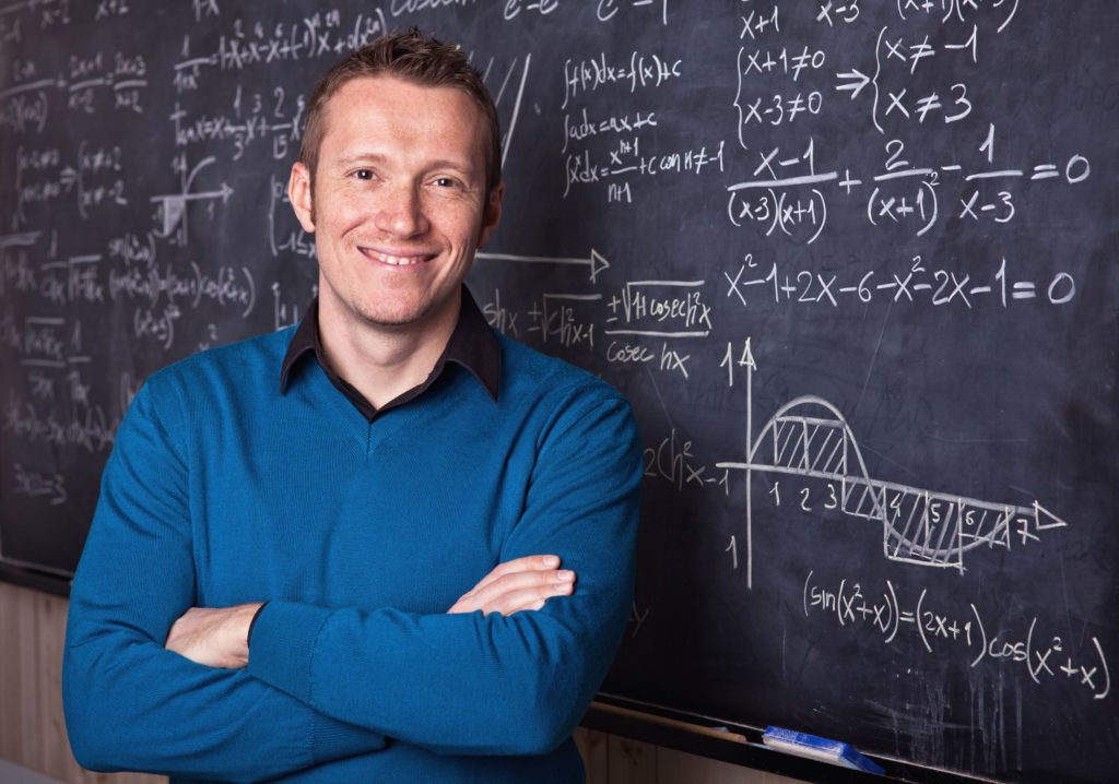 Male teacher standing in front of a blackboard filled with difficult math problems.