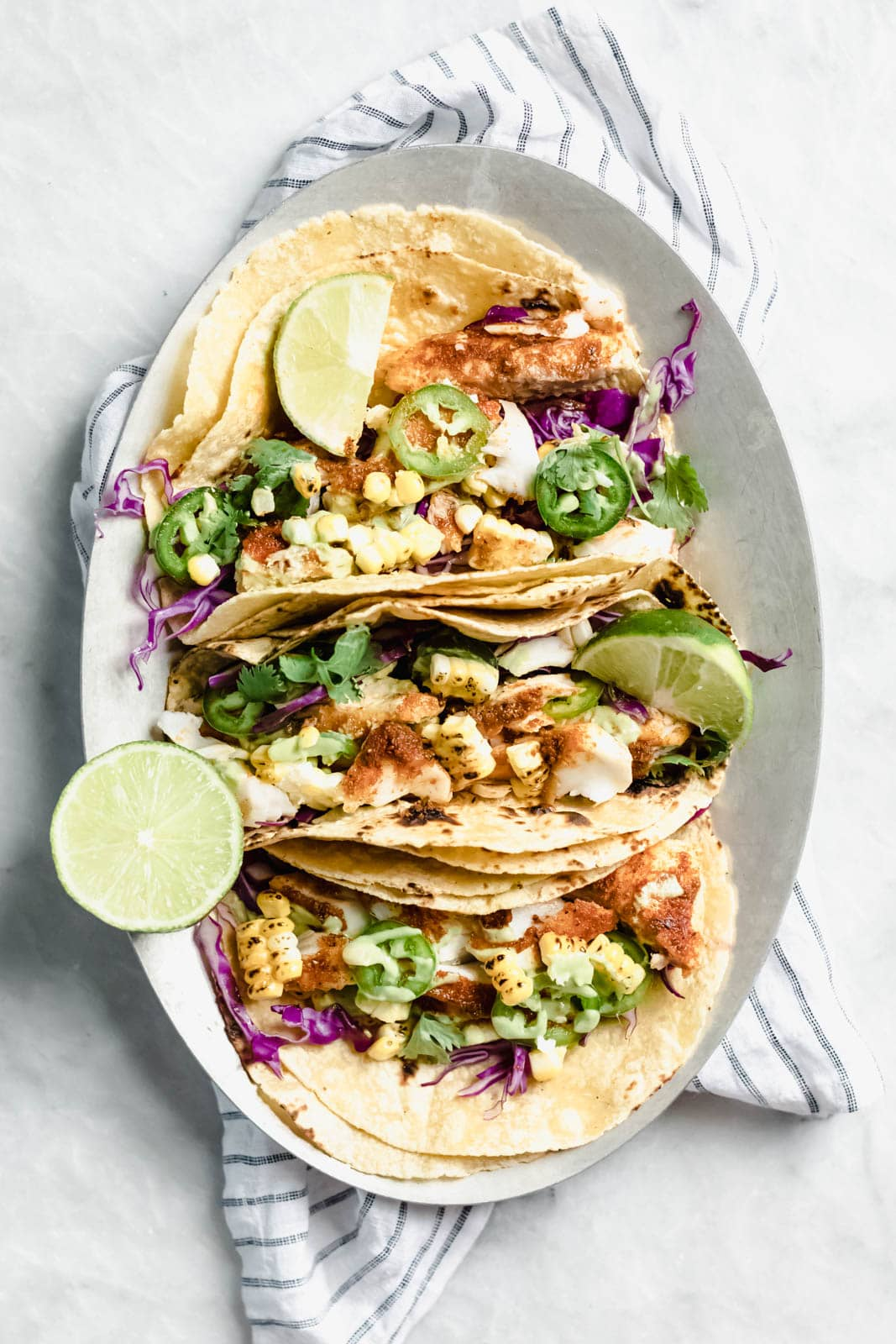 "My go-to recipe for Taco Tuesday fish tacos: flakey blackened fish, cabbage, charred corn, jalapeños, and a ""creamy"" dairy-free avocado cilantro crema!"