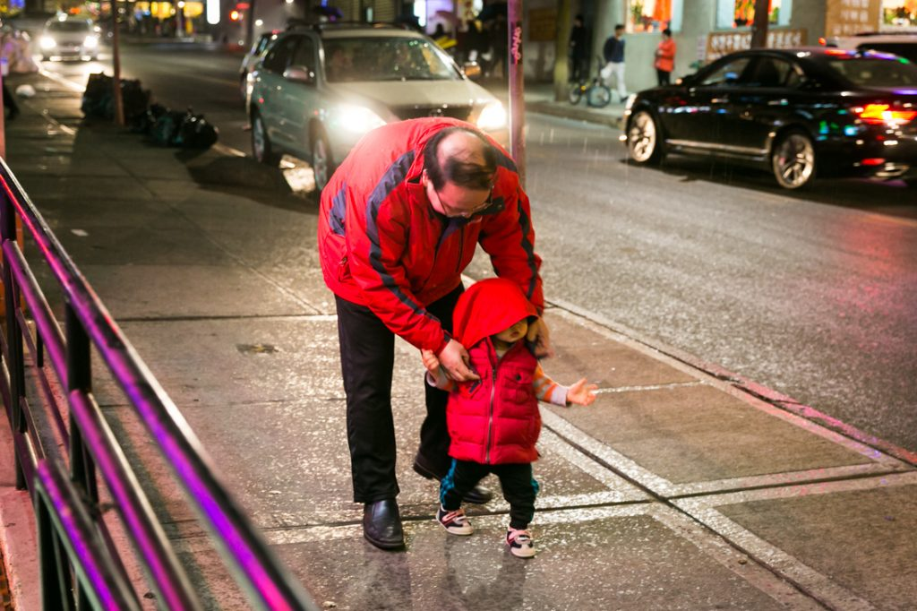 Father and child on the sidewalk in Flushing Queens street photography series
