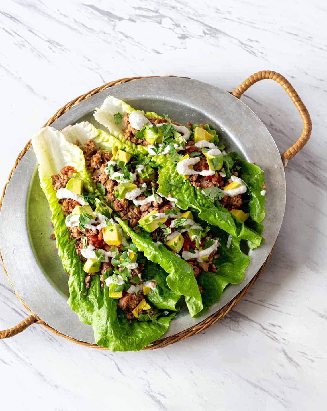 Image of pinto pecan lettuce boats on a metal tray with rattan handles on marble background