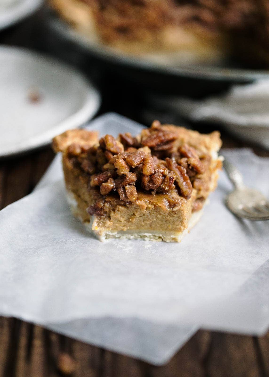 Maple pecans meet a boozy bourbon pumpkin filling in this maple bourbon pecan pumpkin pie worthy of any Thanksgiving dessert table.