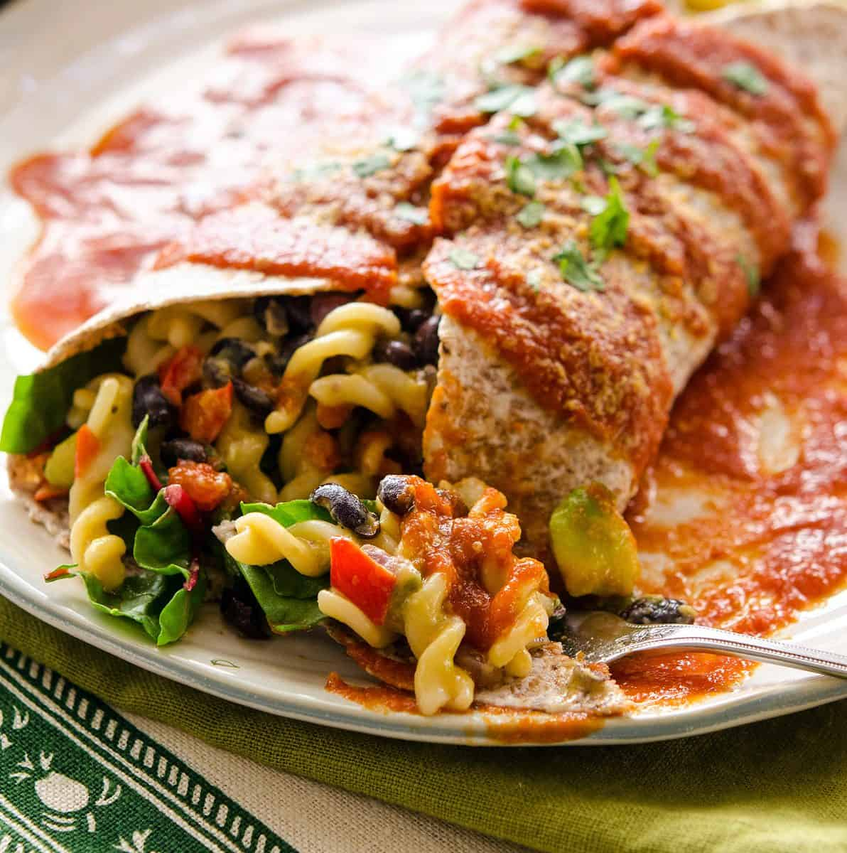 A large burrito stuffed with Mac and cheese and topped with red sauce
