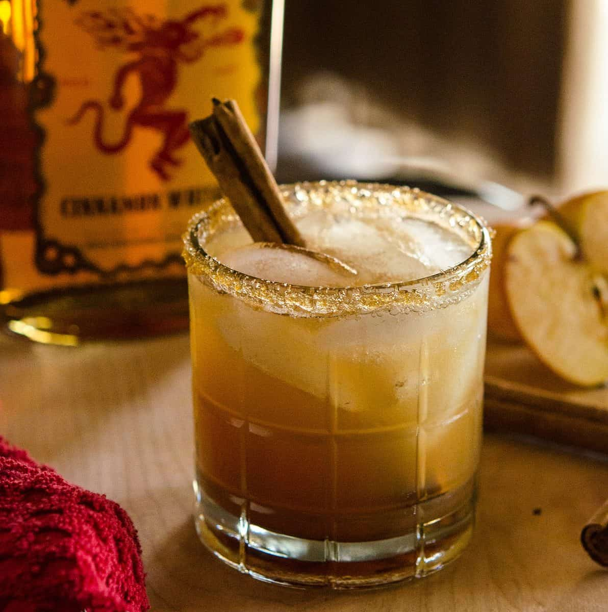 Image of apple juice-based cocktail with cinnamon stick garnish