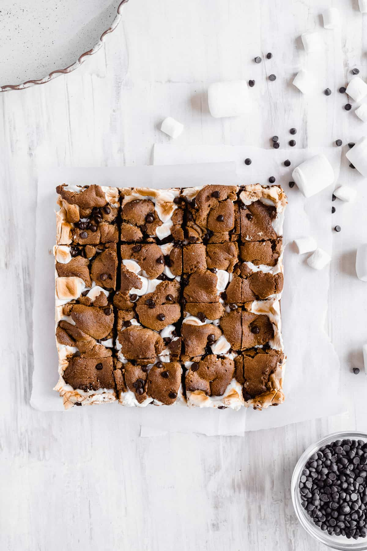 Baked s'more bars on a white sheet sliced into squares.