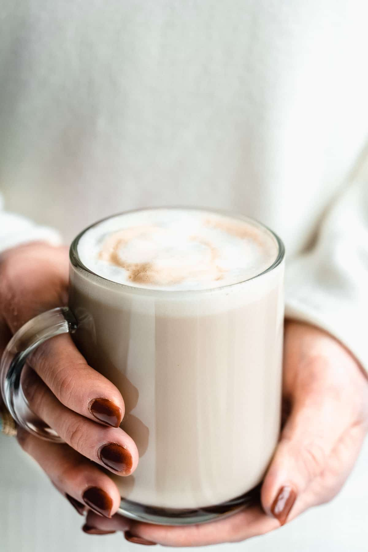 Close up image of two hands holding a cup of Maple Sea Salt Almond Milk Latte.
