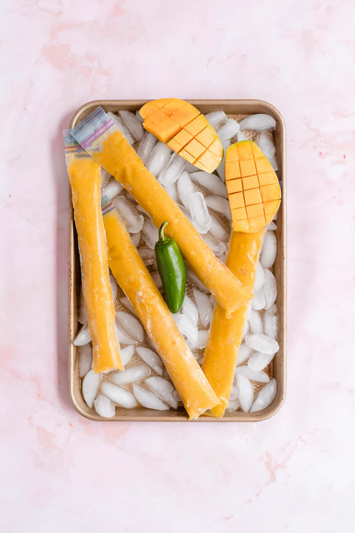 Frozen orange ice pops on a sheet with ice.