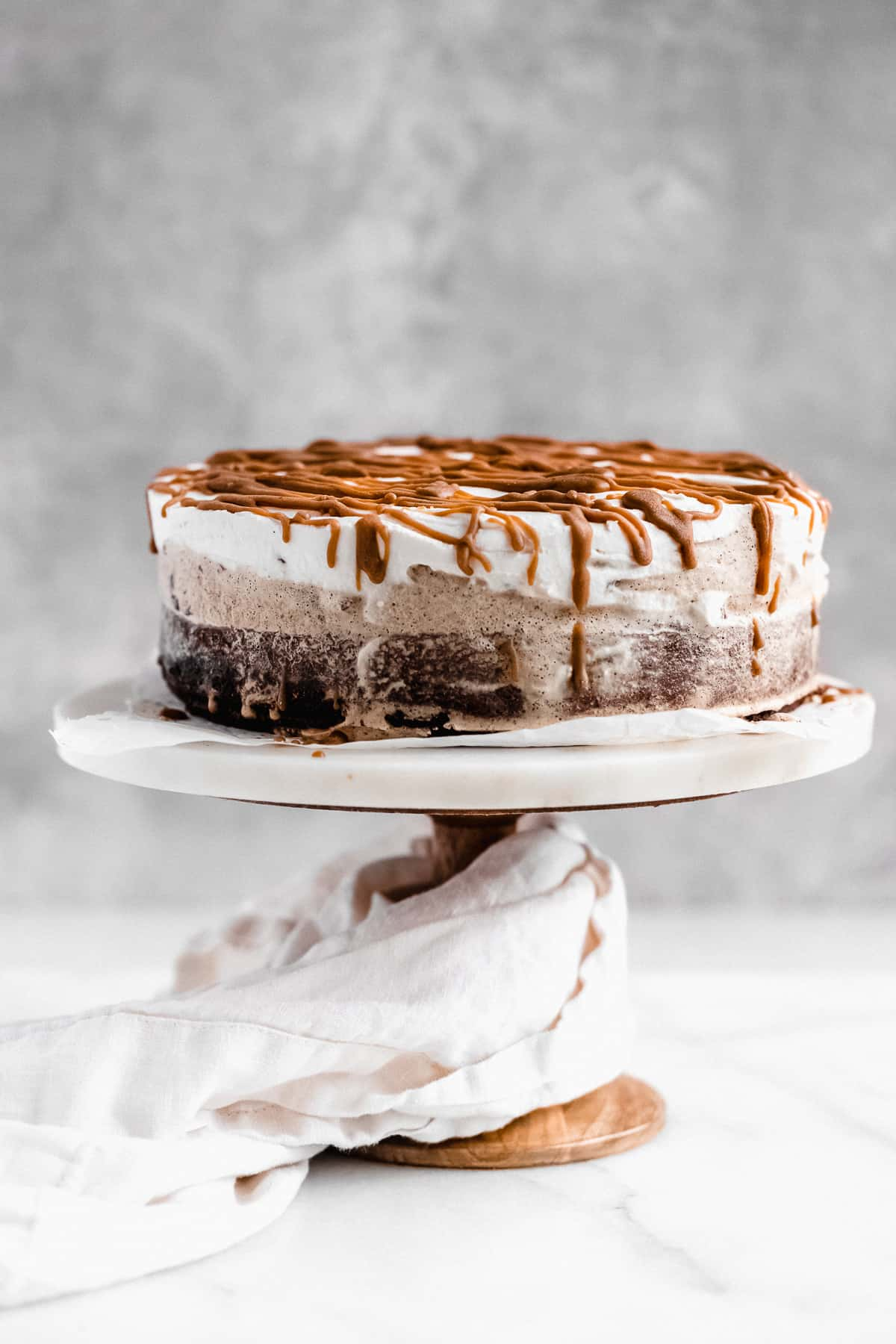 Side view image of the completed Chocolate Espresso Gluten-free Ice Cream Cake sitting on a white marble cake plate with a white linen cloth draped around the base.