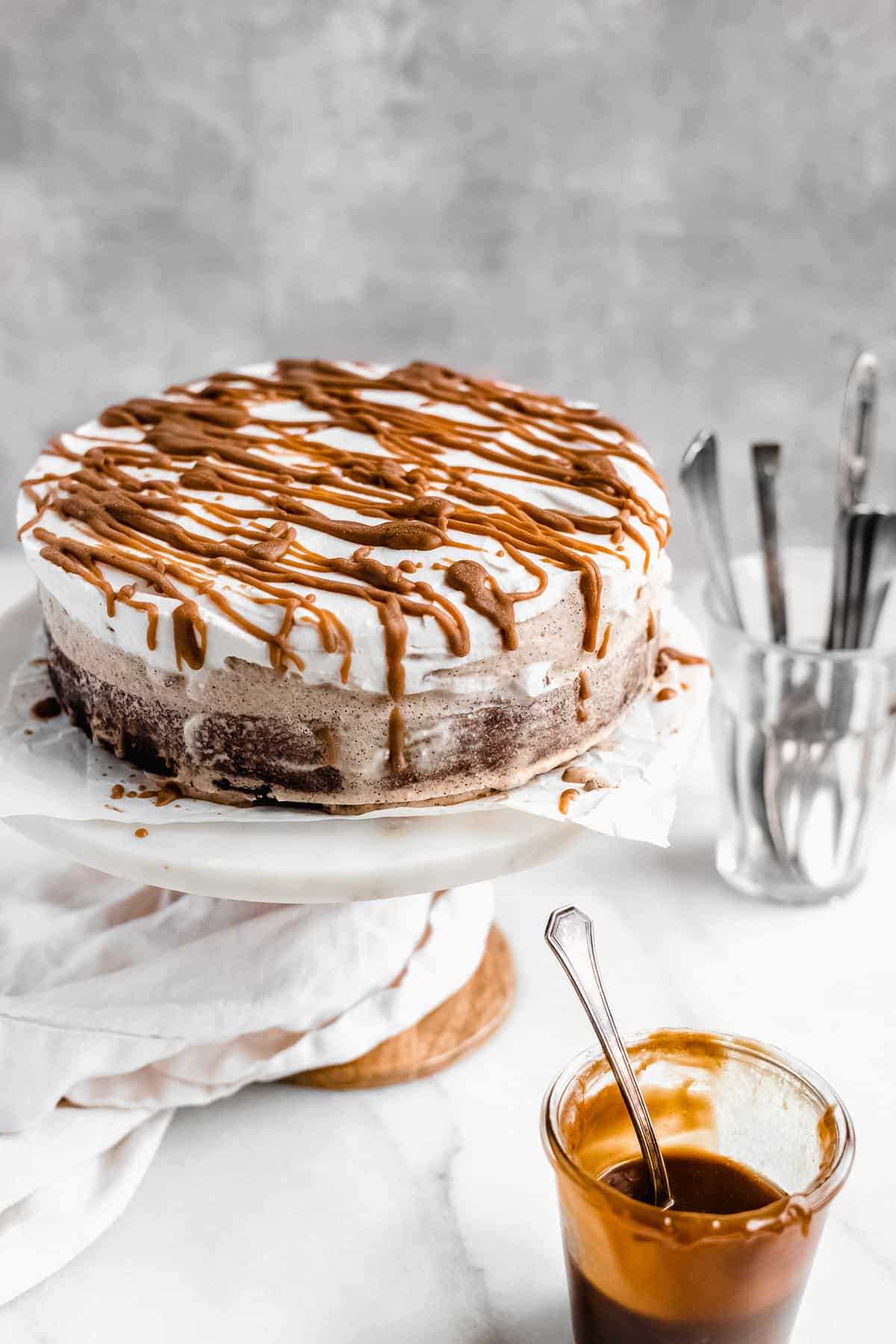 Side view photo of completed cake sitting on a white marble cake plate.  A jar of caramel sauce and a glass with utensils can be seen in the background.