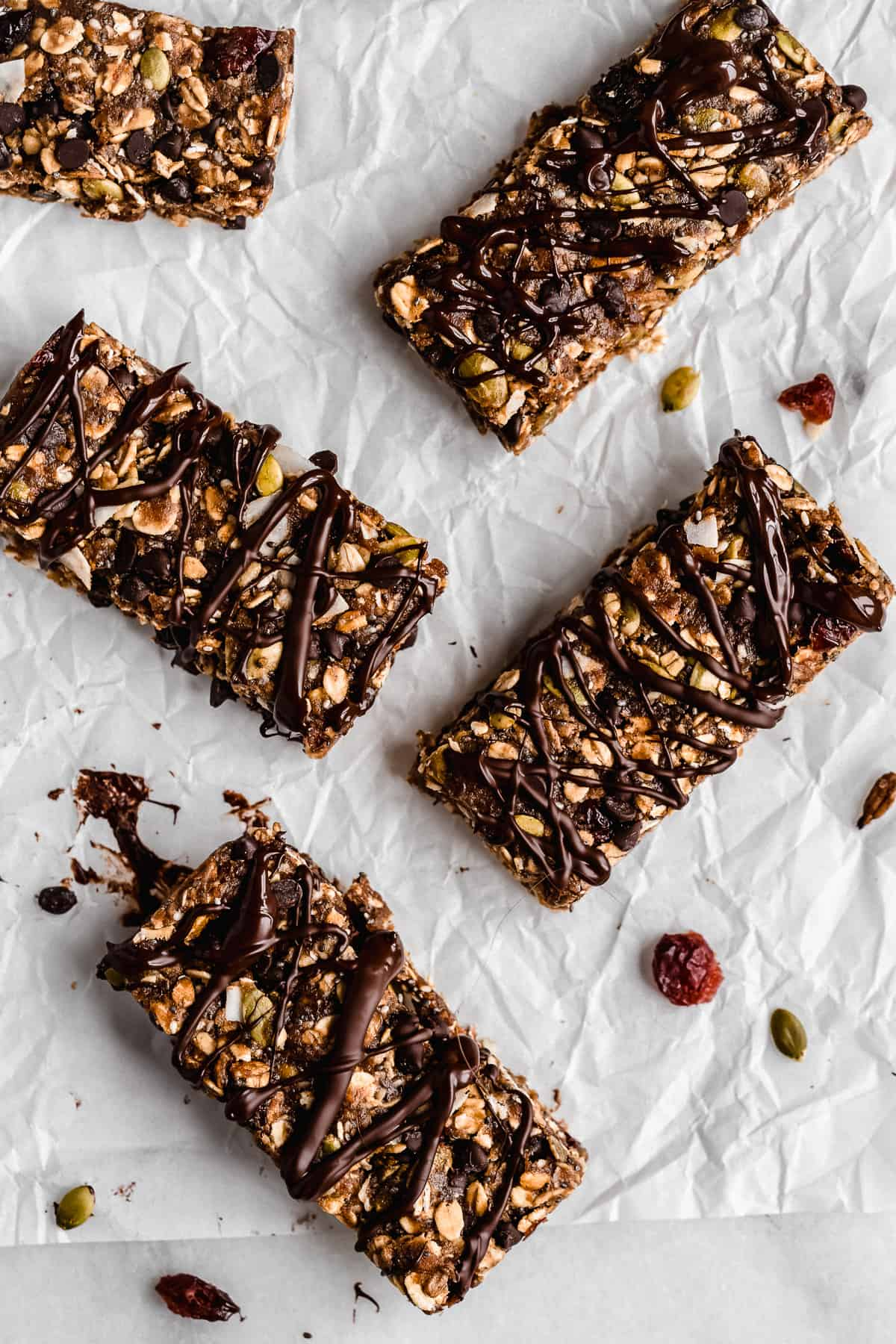 Overhead photo of several Nut-free Chocolate Granola Bars arranged on white parchment paper.