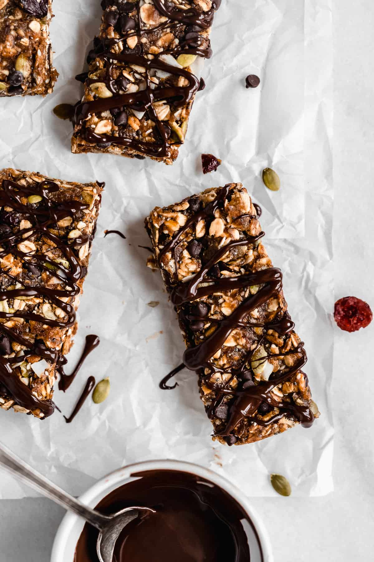 Overhead photo of several Nut-free Chocolate Granola Bars sitting on white parchment paper.  A white bowl of melted chocolate with a spoon sits nearby and has drizzled chocolate on top of the bars.