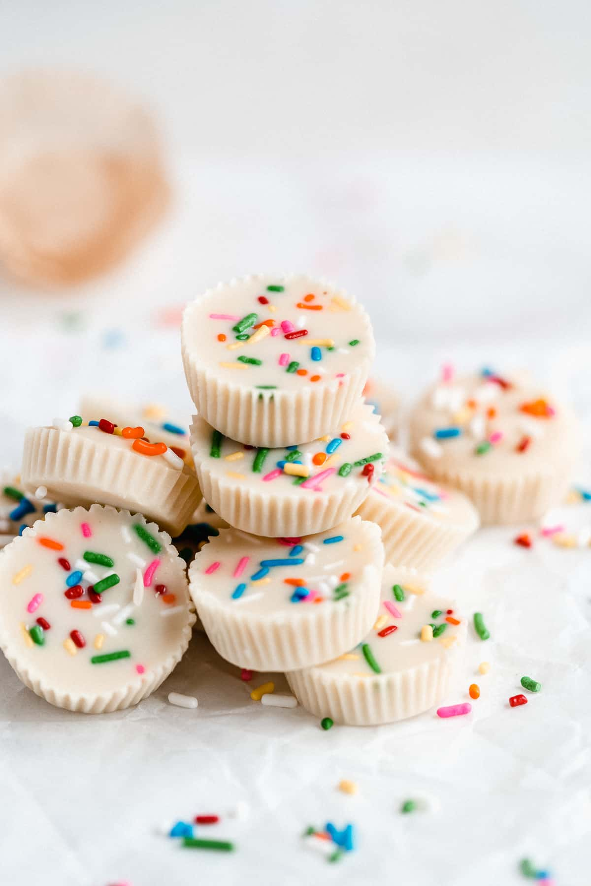 Pile of white chocolate peanut butter cups on white parchment paper with rainbow sprinkles