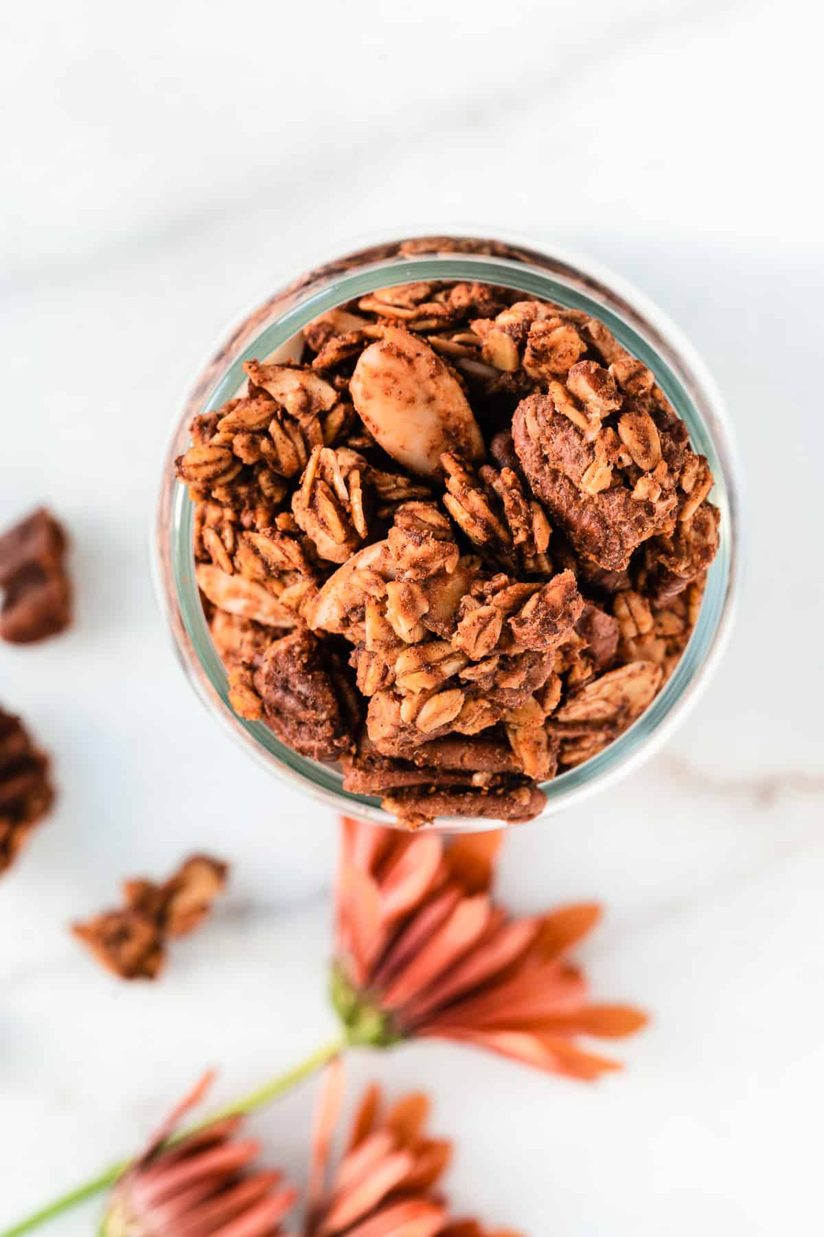 Overhead shot of jar full of pumpkin spiced granola with pecans and orange flowers on surface