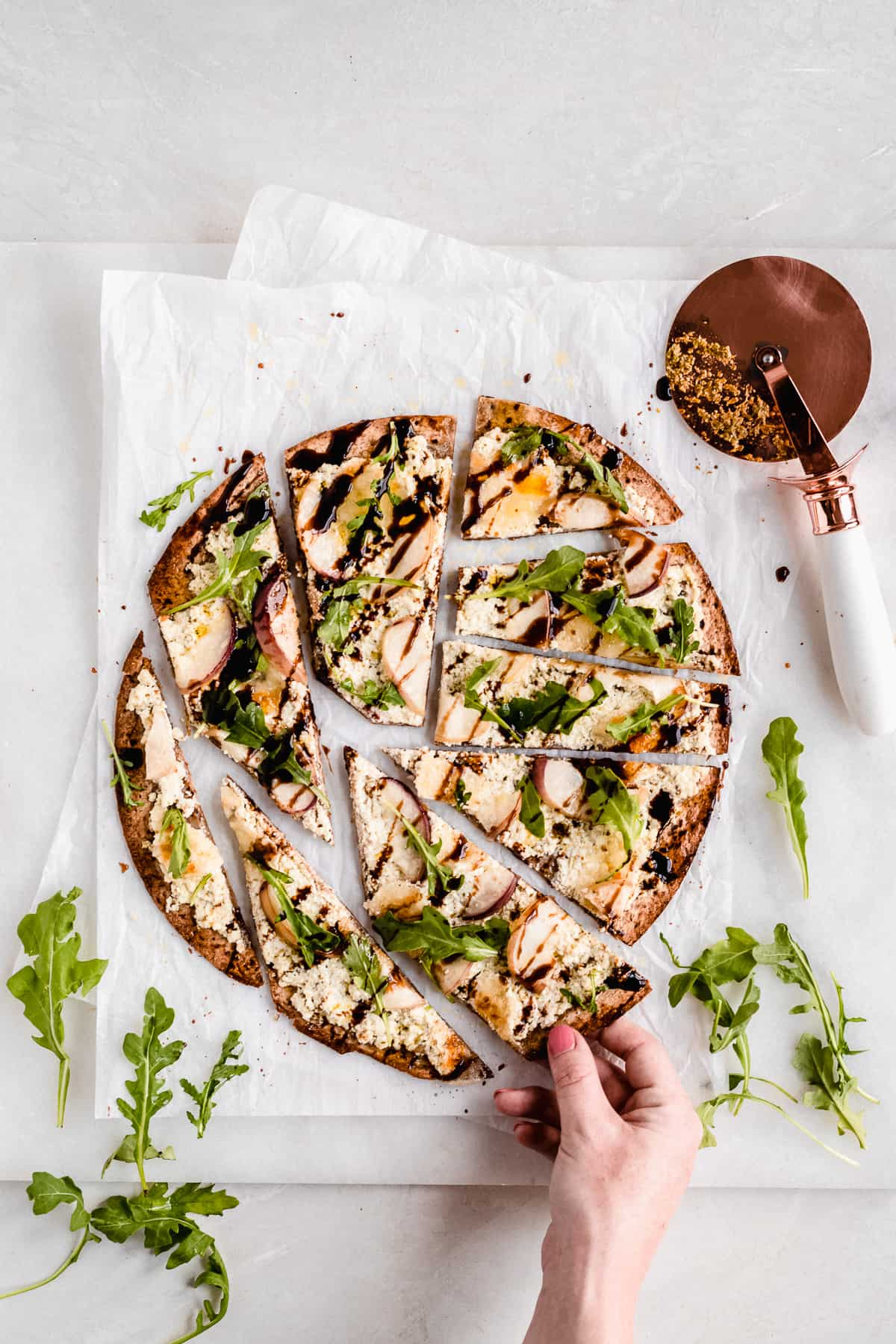Overhead photo of a Crispy White Peach and Ricotta Pesto Flatbread with Balsamic Glaze placed on top of white parchment paper on a marble slab that has been cut into slices that are separated.  A pizza cutter is laying nearby.  A hand is pulling one piece away.