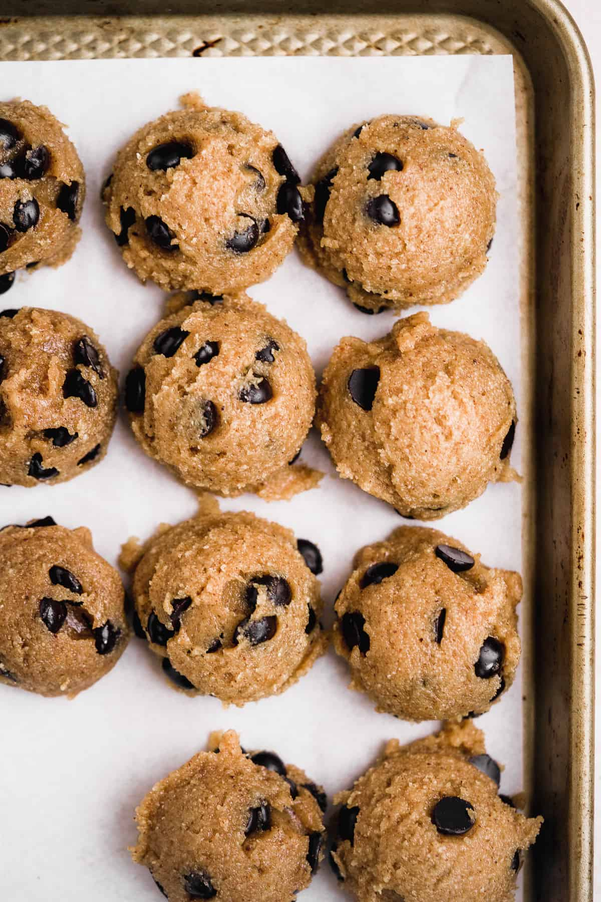 Overhead photo of cookie tray lined with parchment paper and the scoops of Almond Butter Chocolate Chip Cookie dough waiting to be baked in the oven.