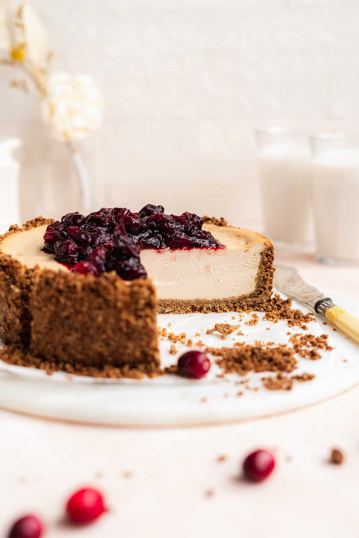 Side photo of Vegan Baked Cranberry Cheesecake with Graham Cracker Crust with a section removed showing the delicious thick cheesecake inside.