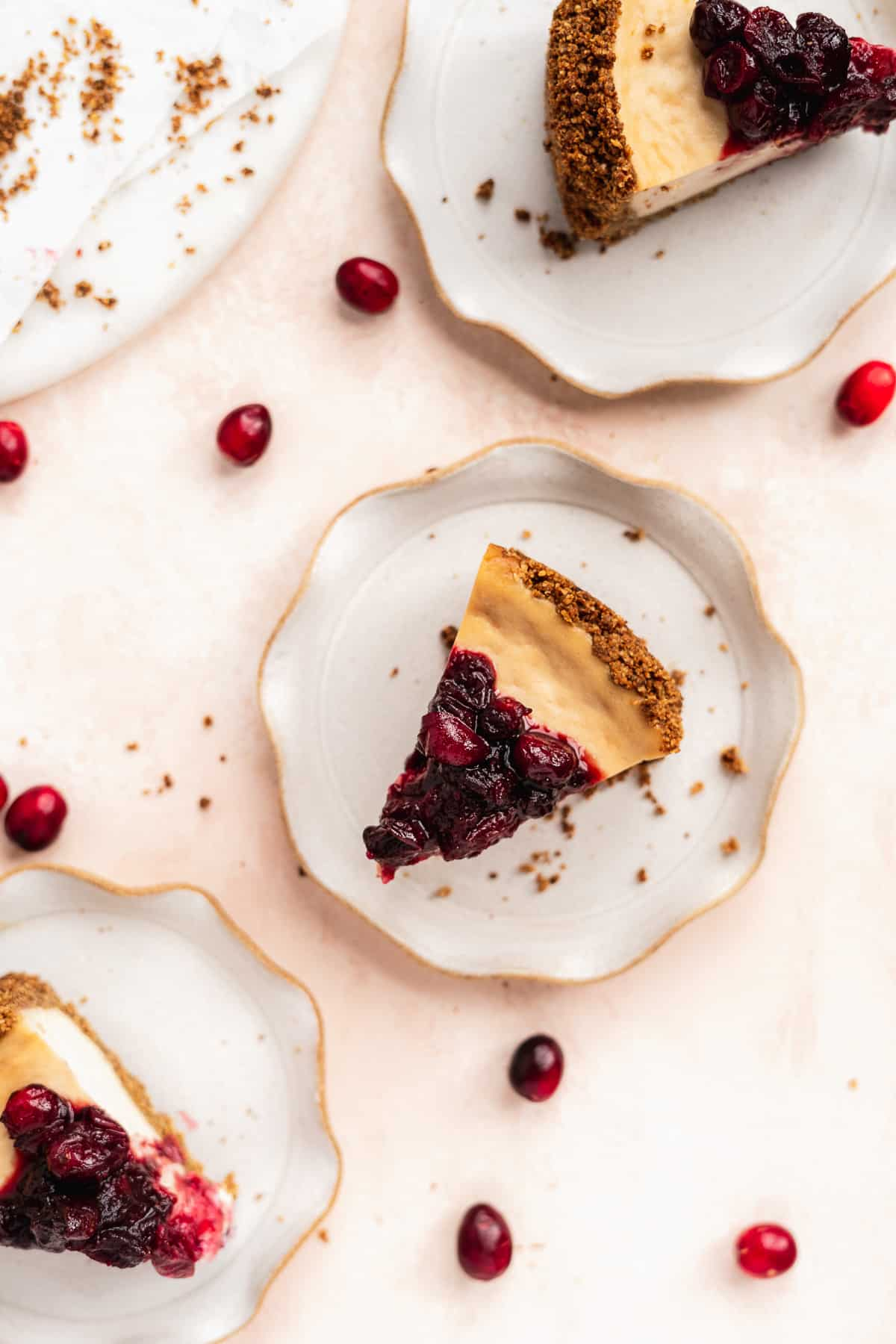 Slices of Vegan Baked Cranberry Cheesecake with Graham Cracker Crust on scalloped plates.  Red cranberries are sprinkled around.