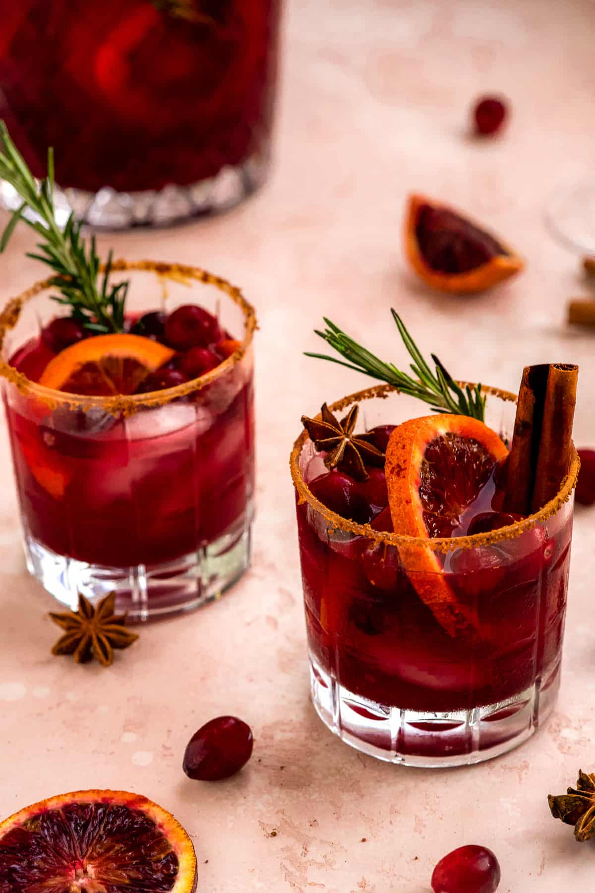 Two crystal cocktail glasses with Blood Orange Cranberry Sangria ready to be enjoyed.  Cranberries are sprinkled around the base of the glasses.
