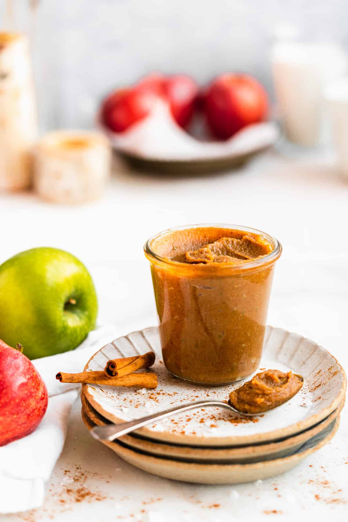 Side view photo of clear jar of Easy Salted Caramel Apple Butter sitting on a stack of 3 grey scalloped plates.  A silver spoon with a scoop of apple butter rests on the plate.  A green and red apple are in the background.
