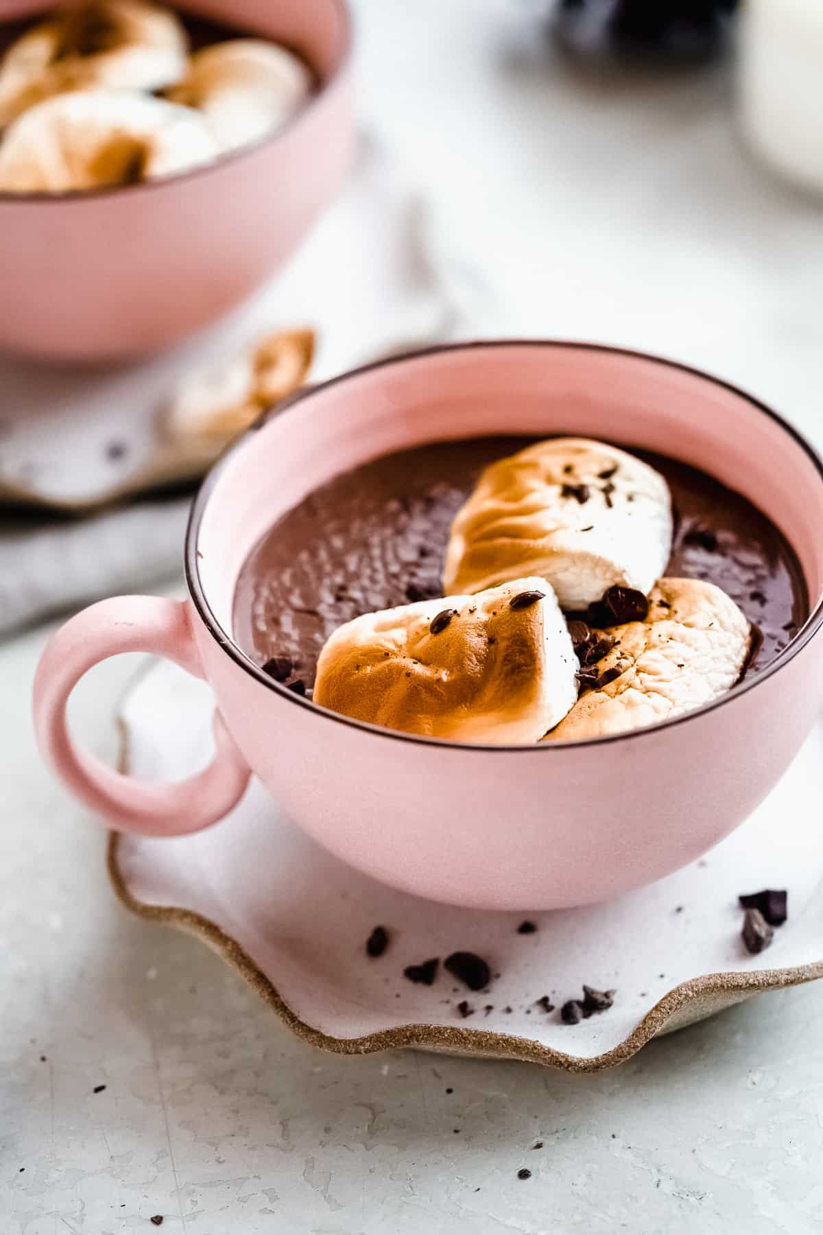 Close up photo of Swoon-worthy Dairy-free Hot Chocolate in a large pink mug with three toasted marshmallows on top.