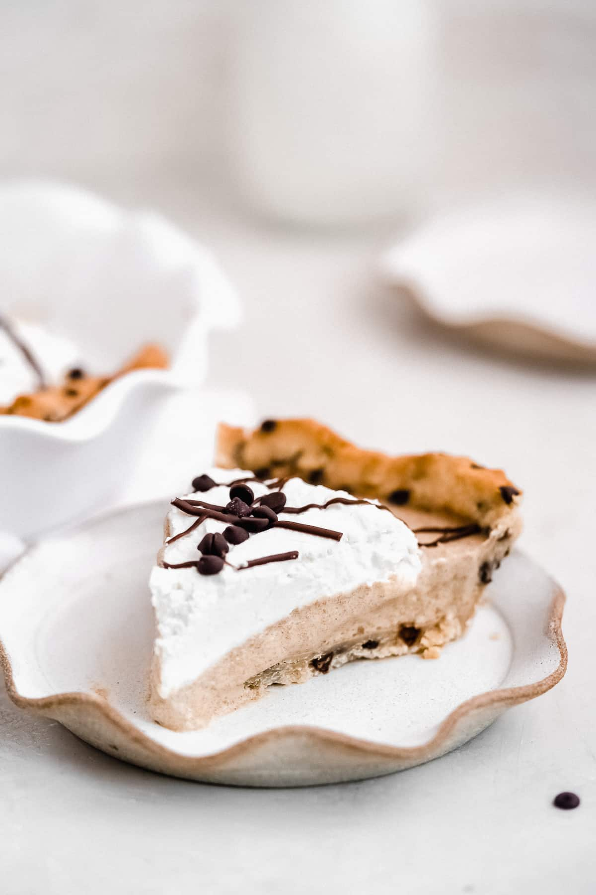 Close up photo of a slice of Peanut Butter Cookie Dough Cream pie on a small scalloped plate.