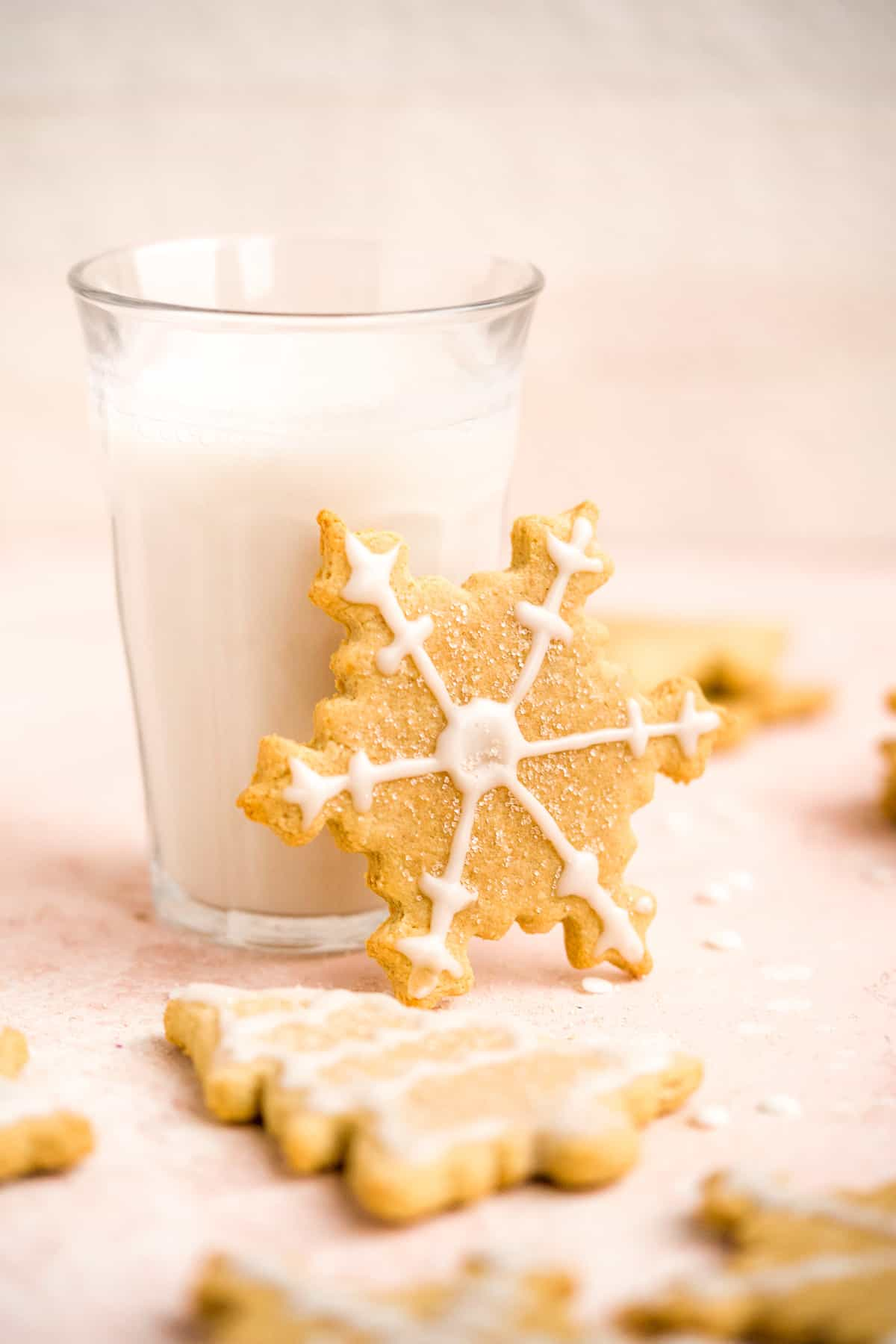 A single snowflake Soft and Crispy Gluten-free Sugar Cookie leaning against a clear glass full of milk.  Additional cookies are laying nearby.