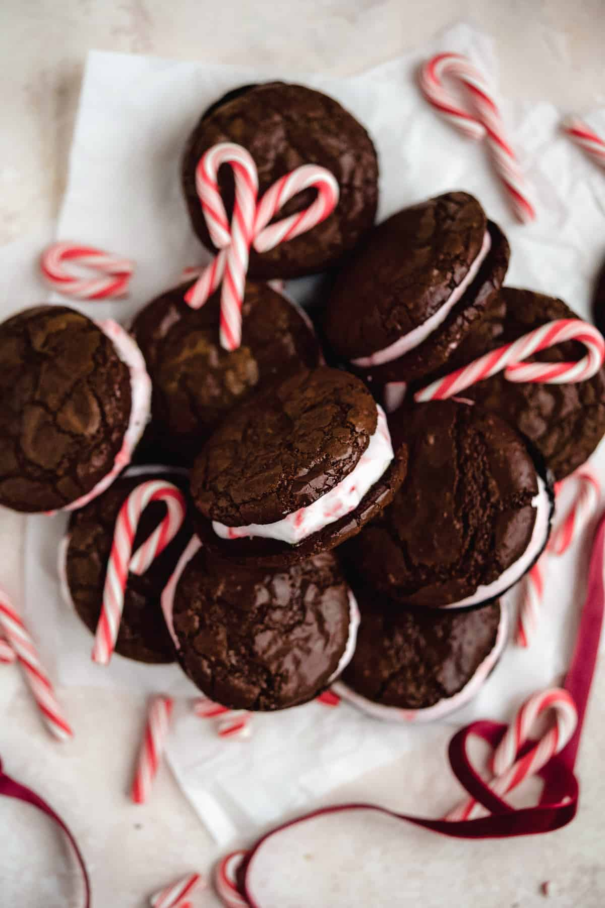 Overhead view of Peppermint Brownie Sandwich Cookies mounded on white parchment paper.  Peppermint candy canes are sprinkled around.