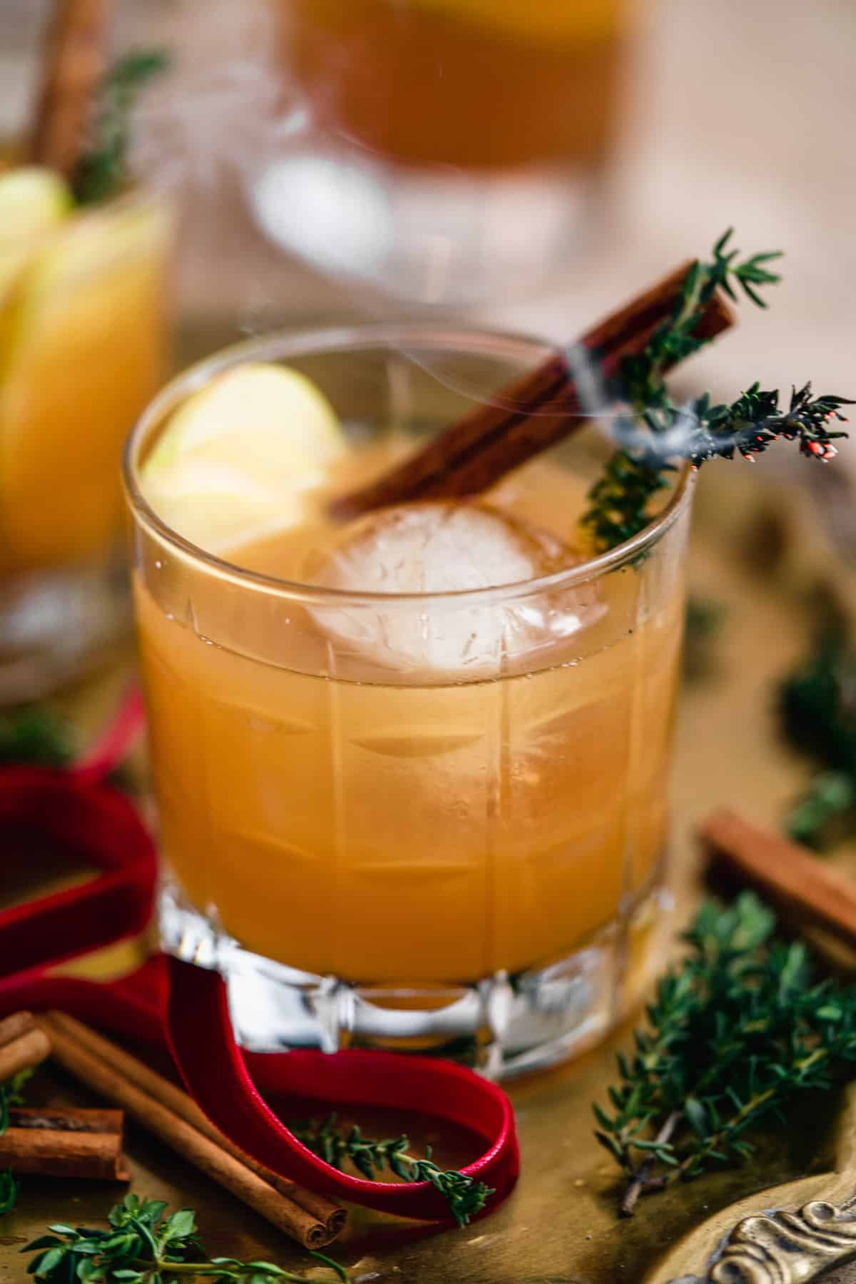 Close up photo of Smoked Cinnamon Apple Cider Bourbon Smash Cocktail in a cut crystal glass over ice with a cinnamon stick and garnish.