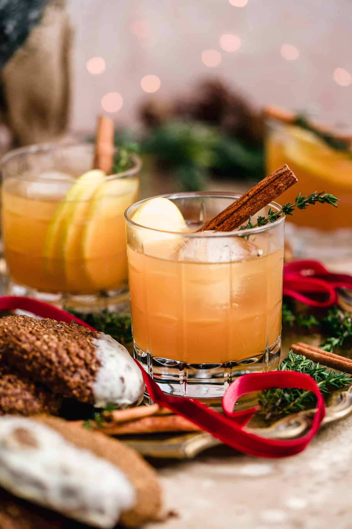 Side view of Smoked Cinnamon Apple Cider Bourbon Smash Cocktails in cut crystal glasses with assorted cookies nearby to enjoy!