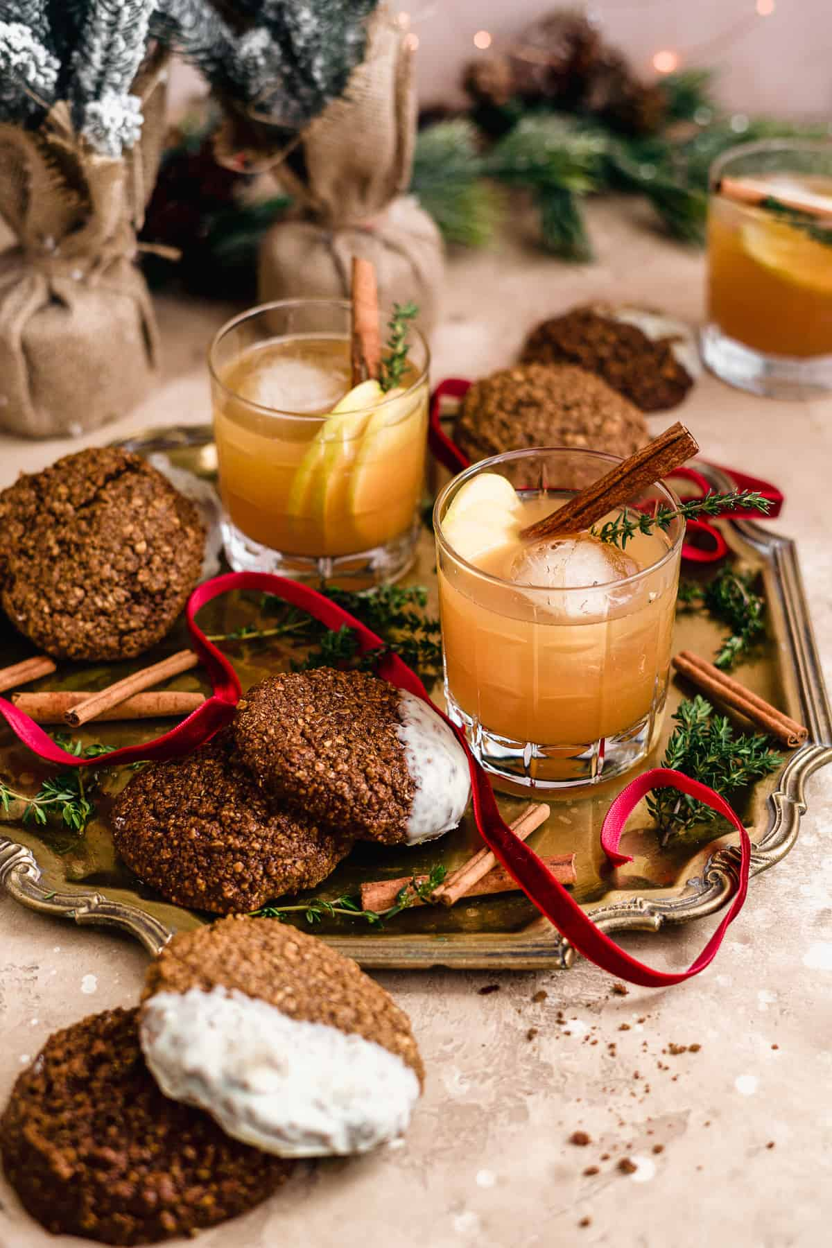 Two Smoked Cinnamon Apple Cider Bourbon Smash Cocktails in cut crystal glasses on a gold tray with cinnamon stick garnish and assorted cookies to enjoy while sipping!