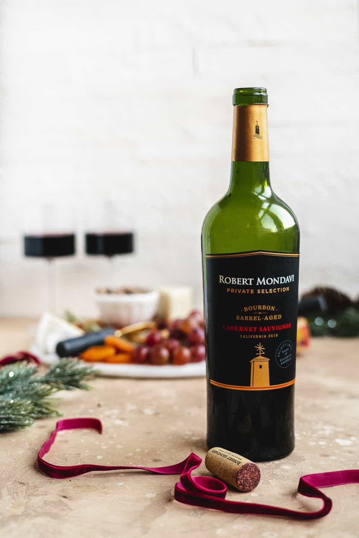 Product photo of Robert Mondavi Cabernet Sauvignon wine bottle with completed charcuterie board in the background.