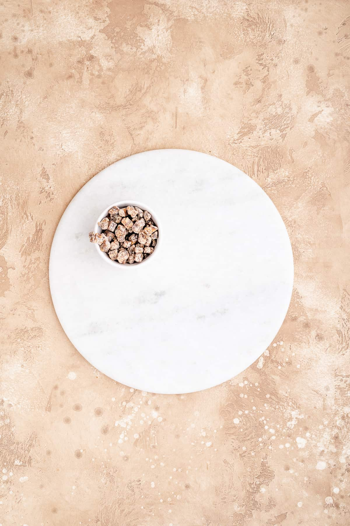 Overhead photo of white marble cake platter with small white bowl of nuts placed on the platter to begin building the charcuterie board.