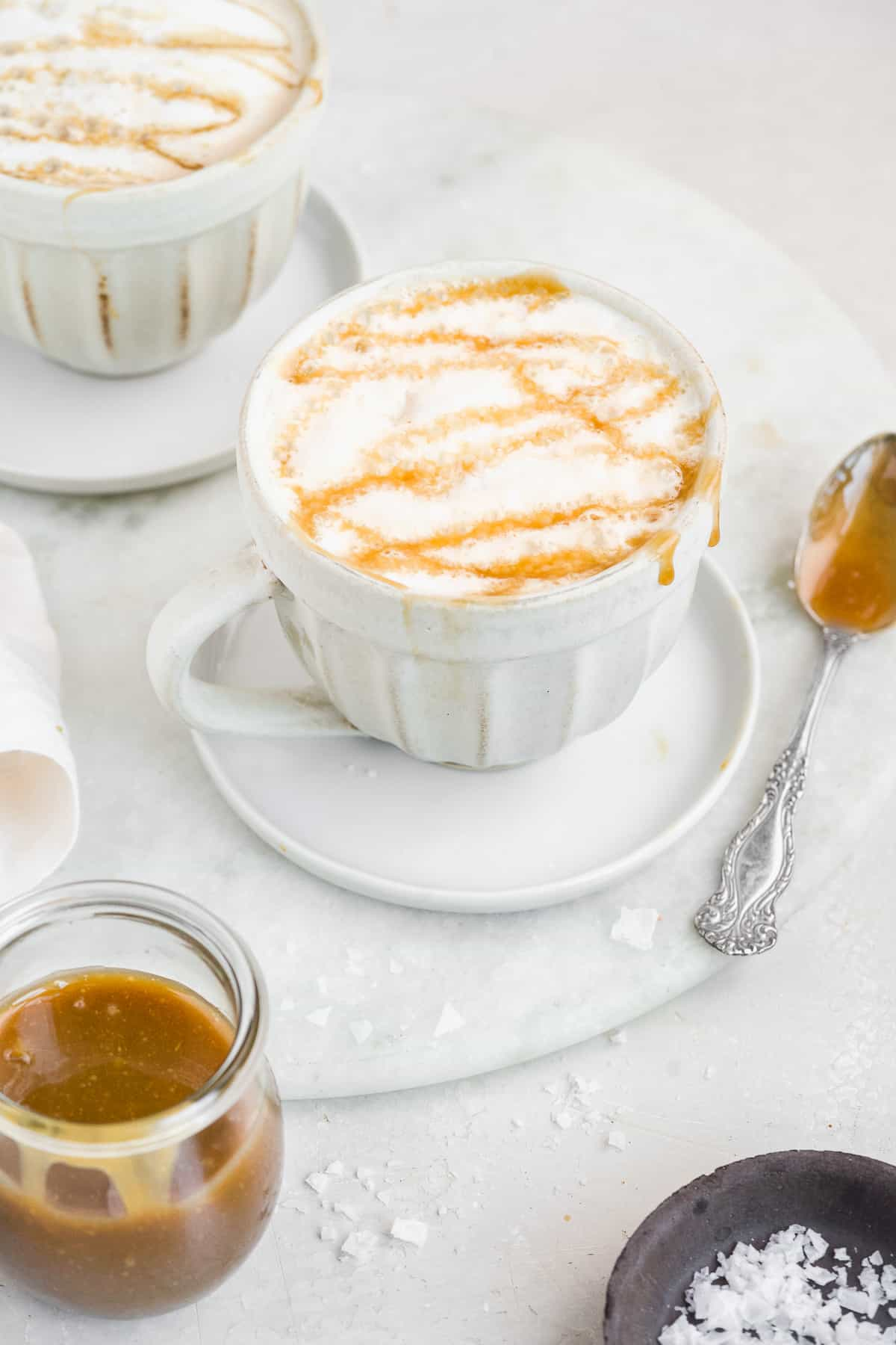 Two white mugs with frothed milk and caramel dripping over the sides on white marble.