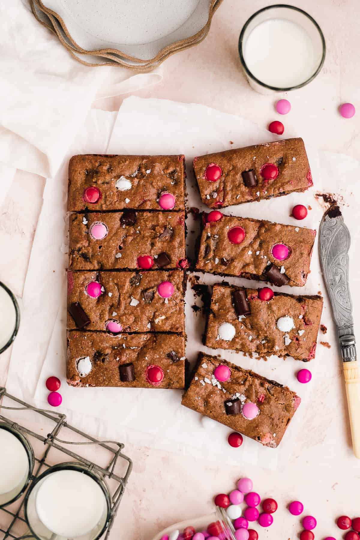 Cookies sliced into bars with red and pink M&Ms on top on white parchment paper.