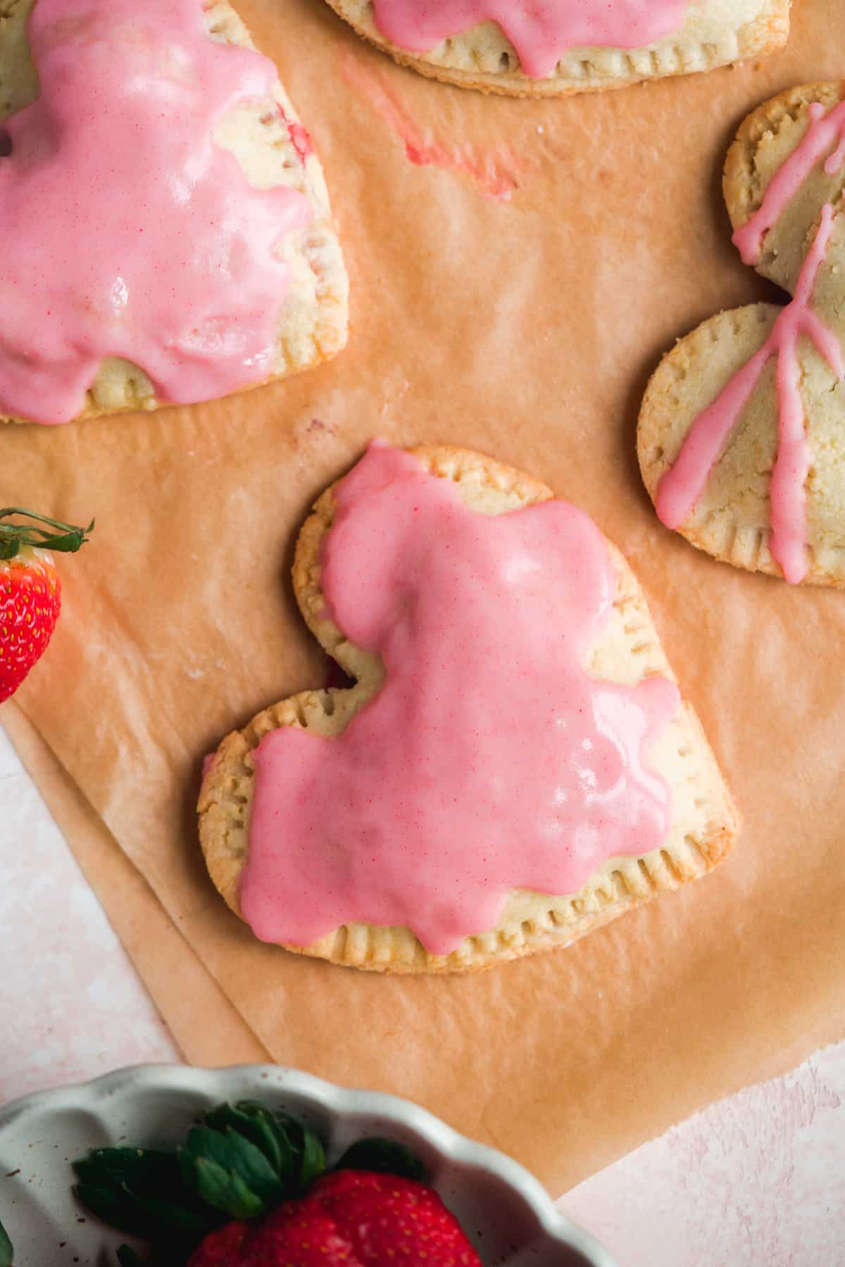 Heart shaped pop tarts on brown parchment paper with pink icing and strawberries in the corner.