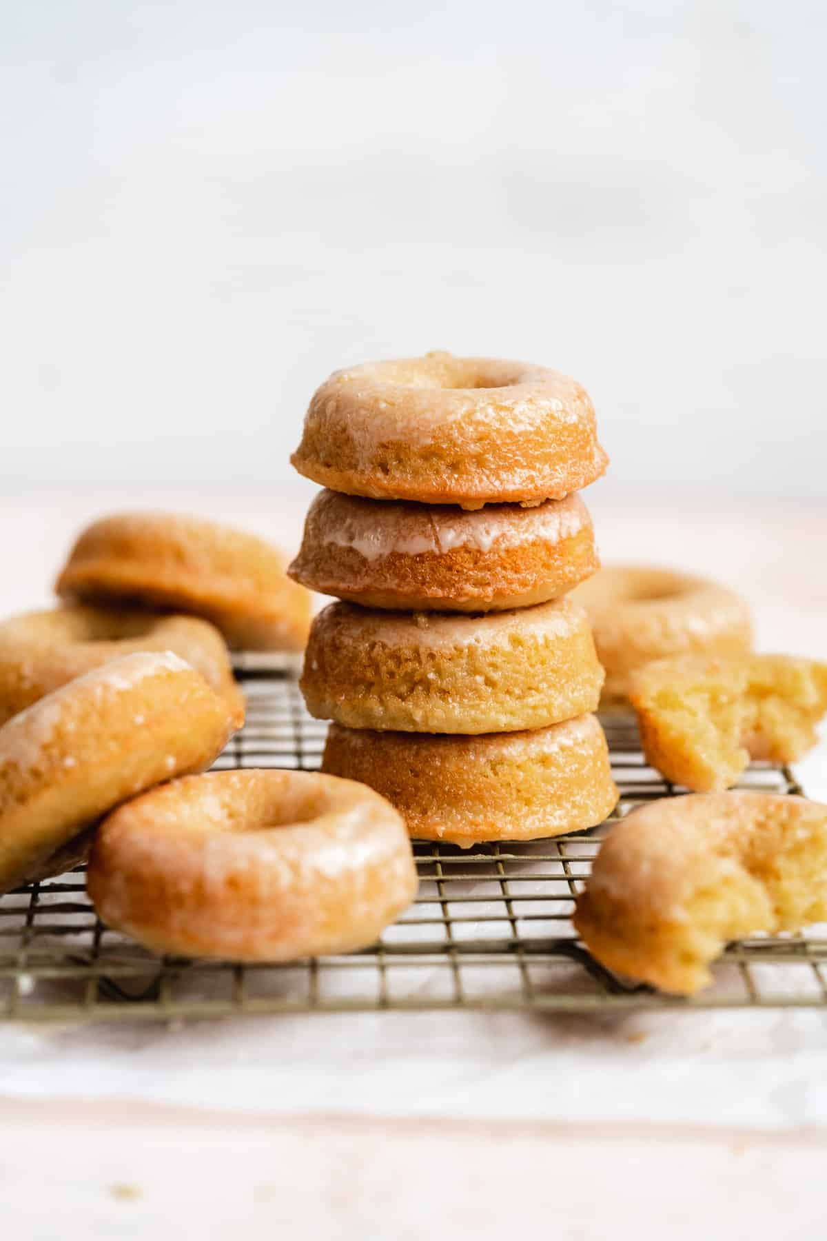 Glazed donuts stacked on a wire rack with donuts scattered on surface.