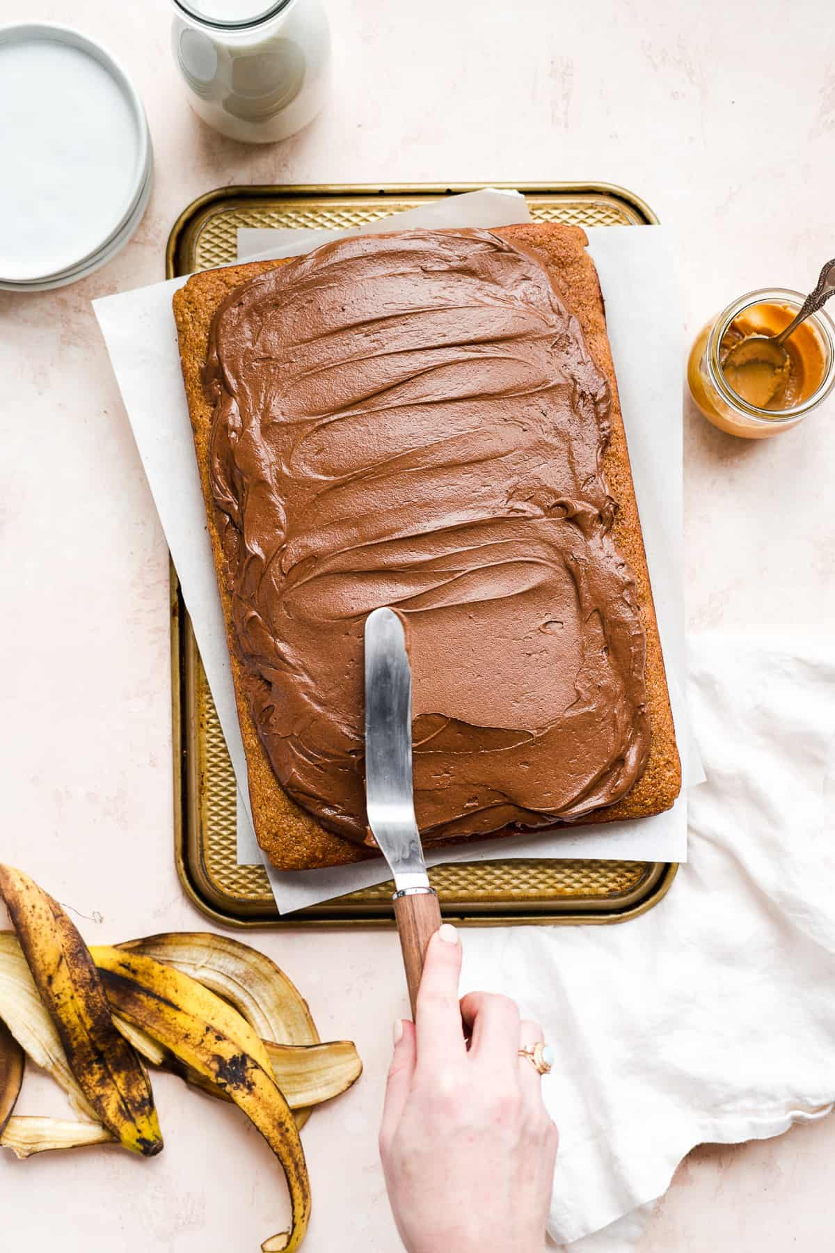 Hand spreading chocolate frosting over top of a cake.