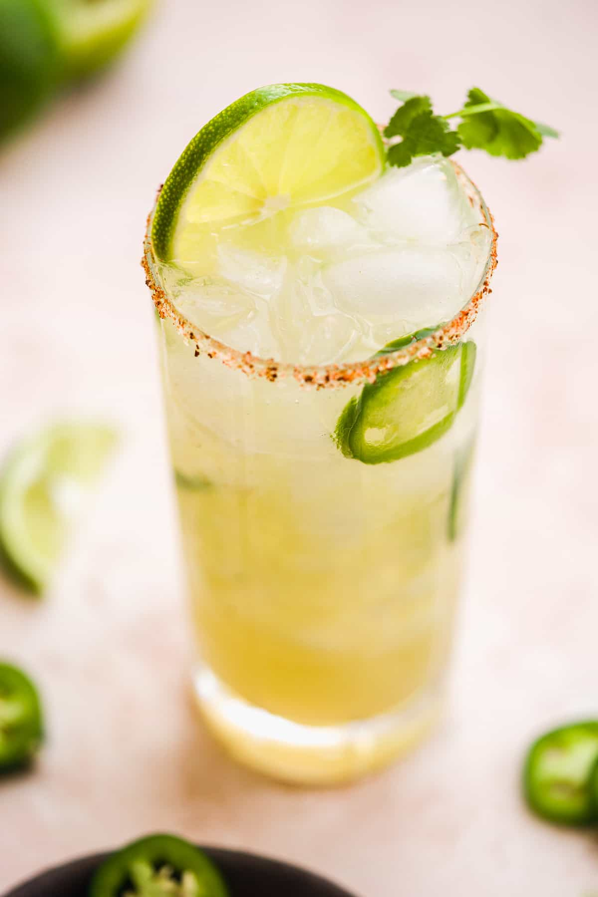 Tall glass of margarita with lime slice on top and a jalapeño and orange salted rim.