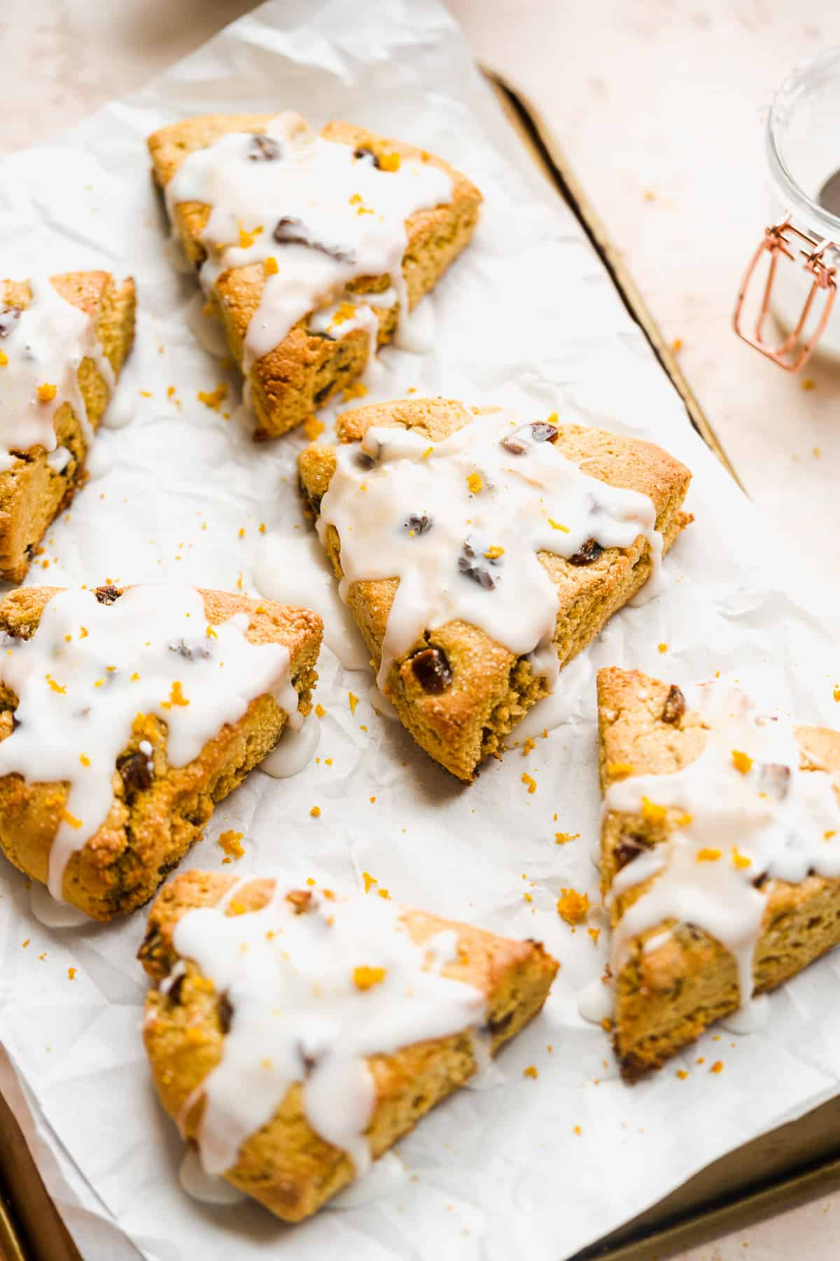 Golden scones with white icing on white parchment paper on top of a baking sheet.