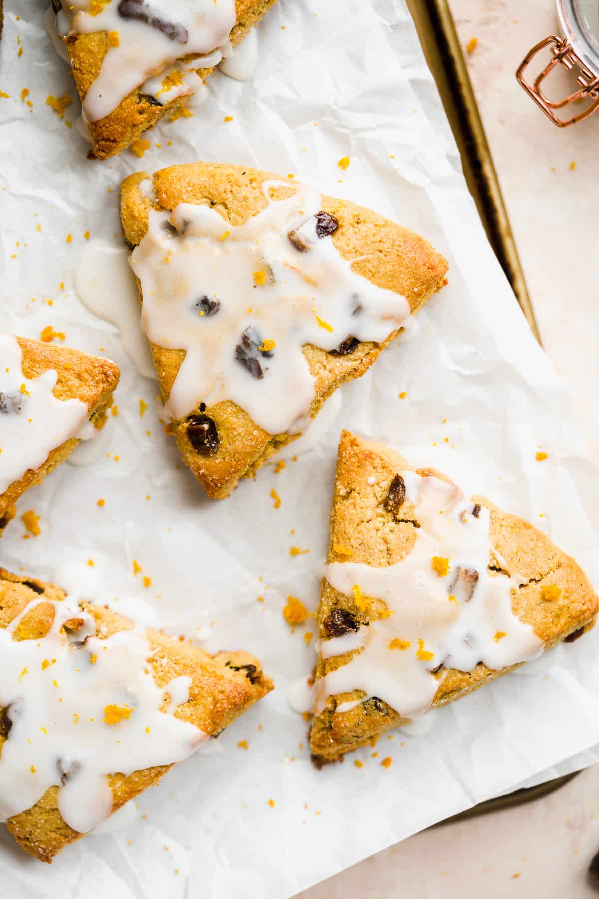 Golden scone with white icing and orange zest on white parchment paper.