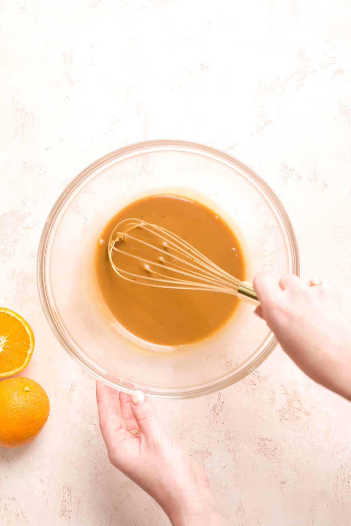 Hand whisking tan mixture in a large glass bowl with an orange off to the side.