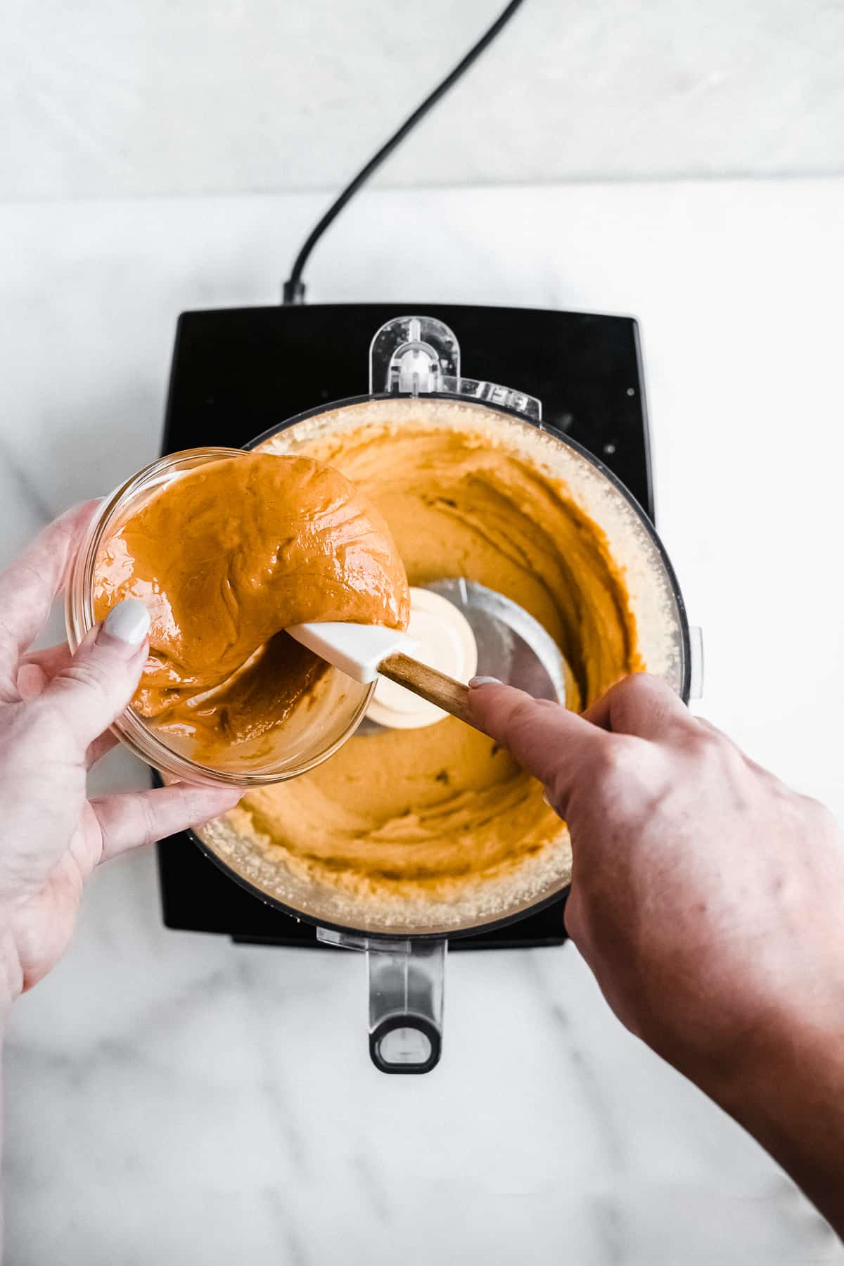 Hand pouring nut butter into food processor with tan mixture inside.