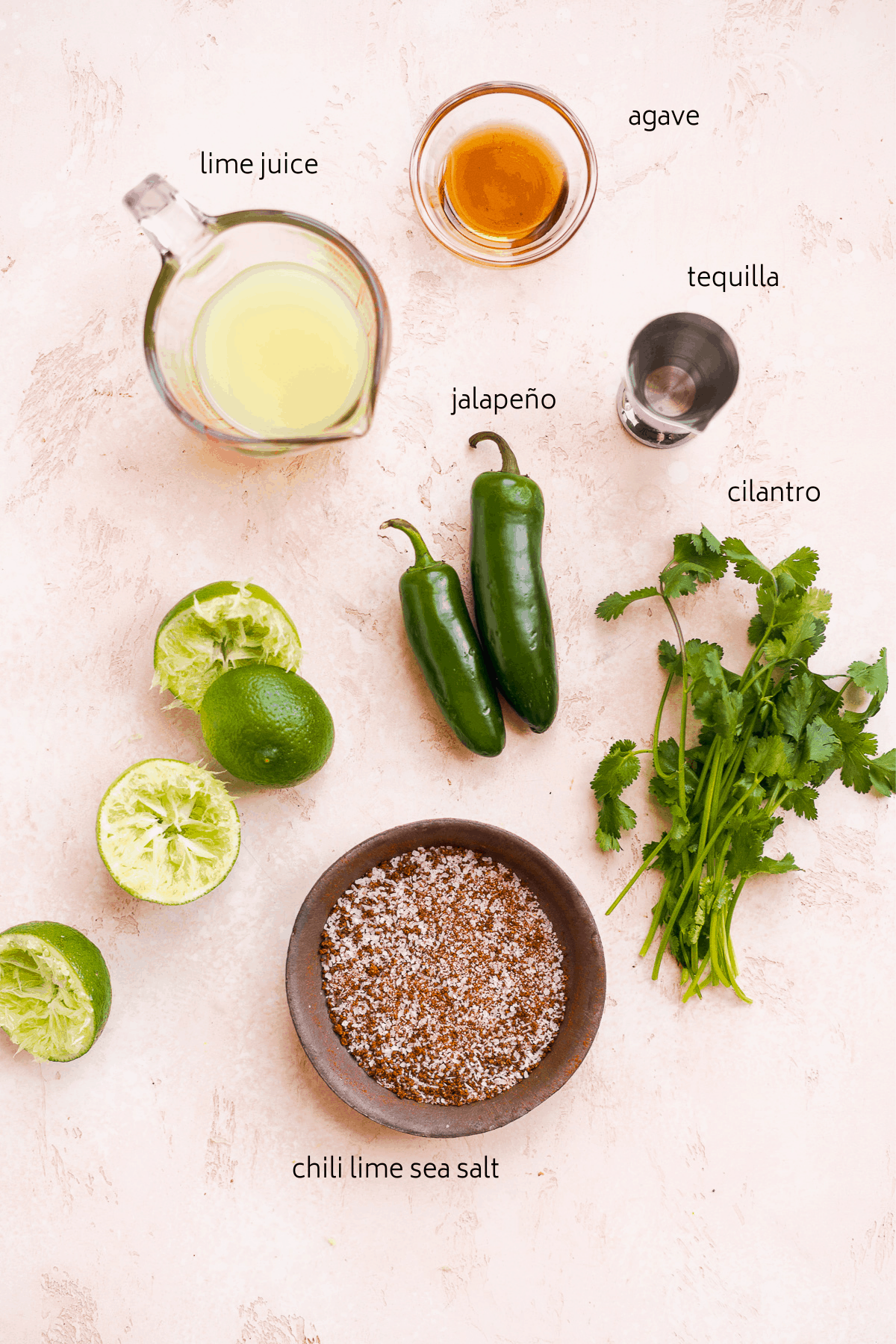 Image of cocktail ingredients with black labels on a dusty pink surface including limes, cilantro, and jalapeño.