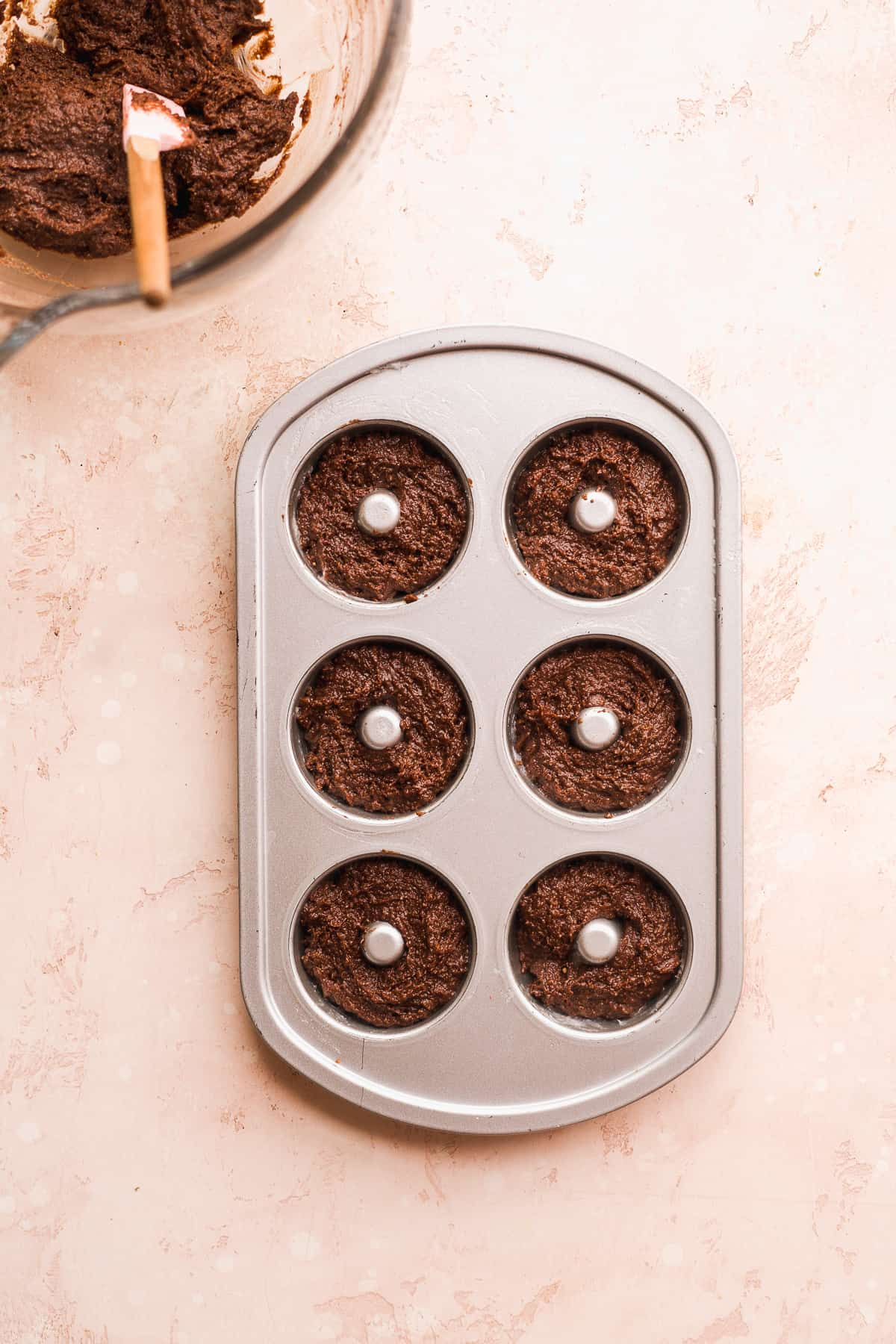 Doughnut pan filled with chocolate batter with bowl off to the side,